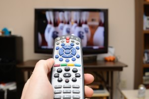 Hand holding remote control toward TV